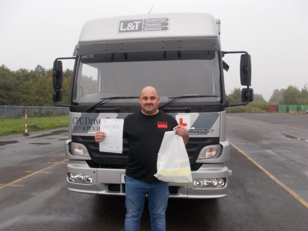 A photo of Andy Bardsley with an L&T vehicle and his pass certificate